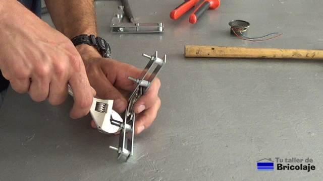 apretando los tornillos para sujetar las partes que formarán la escuadra magnética casera
