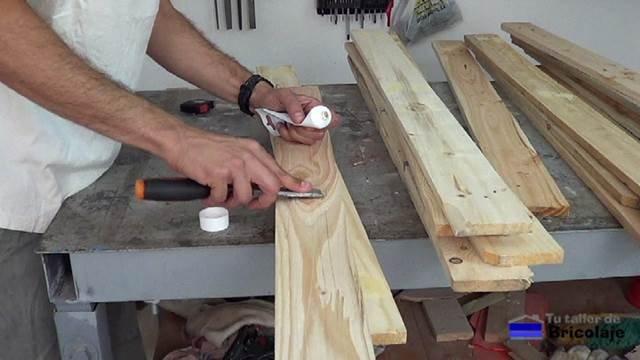 rellenando los agujeros de la madera de palets con masilla