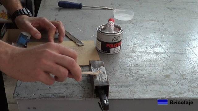 aplicando la fibra de vidrio para tapar o rellenar el agujero en el hierro o metal