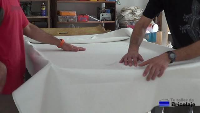 estirando bien el tapizado del techo del coche después de aplicar la cola de contacto