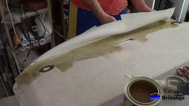 aplicando cola para pegar el tapizado al techo del coche