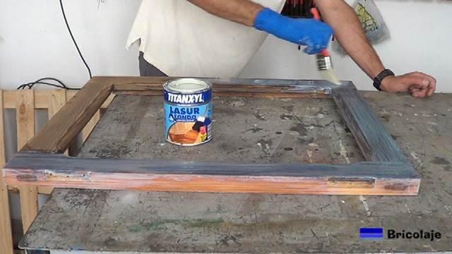 aplicando tapaporos a la vieja ventana de madera