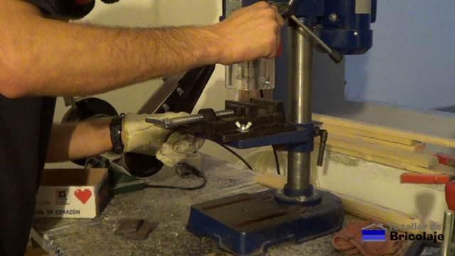 perforando la pletina de hierro con el taladro de columna