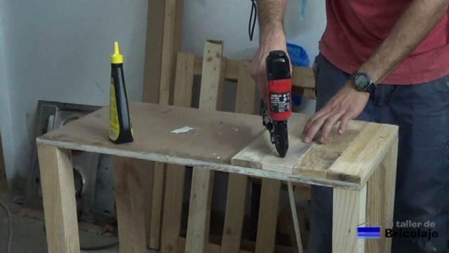 pegando y clavando con tachas o clavos la cubierta superior de madera de palets