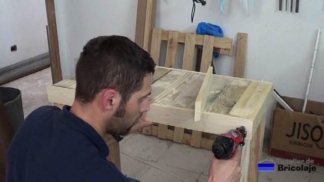 sujetando mediante tachas o clavos las maderas de palets necesarias para hacer la mesa recibidor
