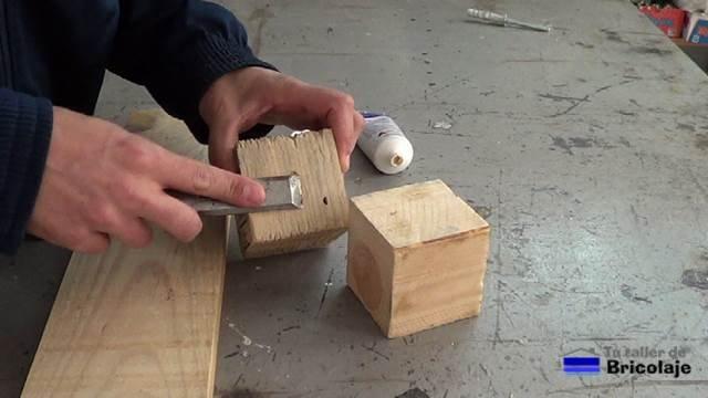 tapando agujeros en los tacos de madera de palets con masilla