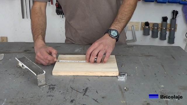 marcando el lugar donde hacer los agujeros en la madera para sujetarla al soporte de pared