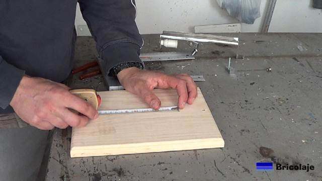 midiendo para marcar el lugar donde hacer los agujeros en la madera