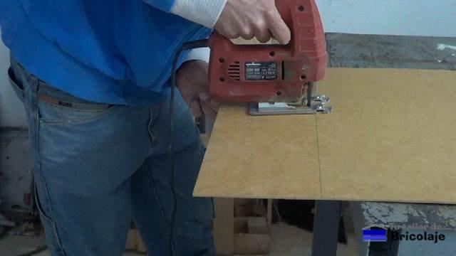cortando con la caladora el suelo de la caja de madera para organizar