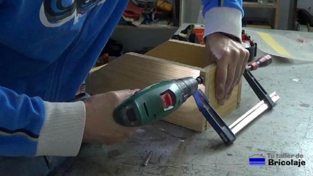 perforando los agujeros para sujetar las piezas de la caja de madera