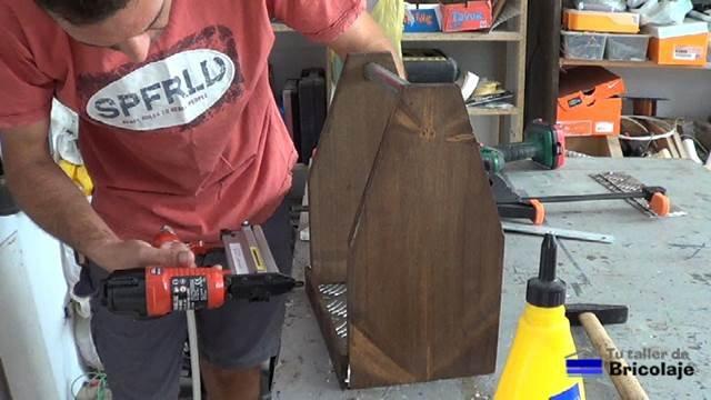 sujetando las piezas que forman el porta cervezas con tachas o clavos