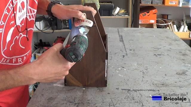 colocando un abre chapas de cervezas en el lateral del porta cervezas