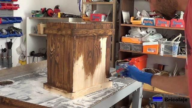 aplicando barniz tinte al cubo de basura de palets