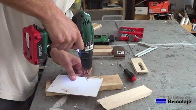 perforando el cartón piedra para poder sujetar el disco duro a la misma