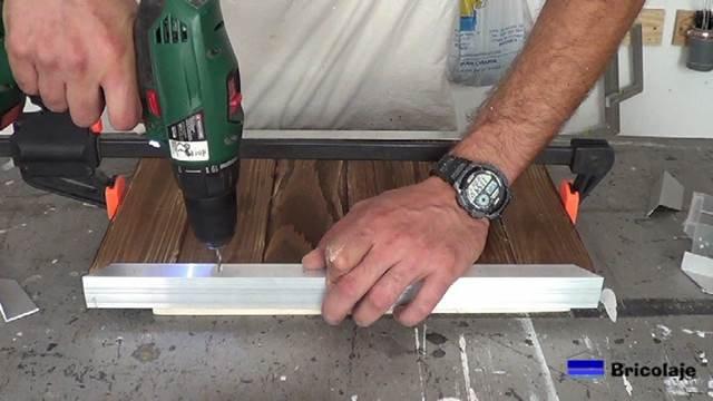 taladrando el ángulo de aluminio para sujetar la madera de palé