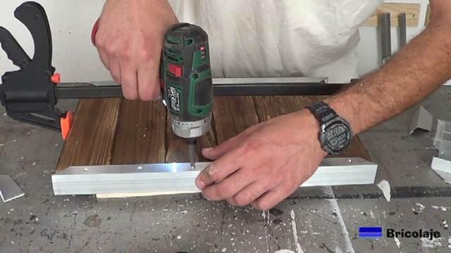 atornillando los agujeros para sujetar la madera de palé a los ángulos de aluminio