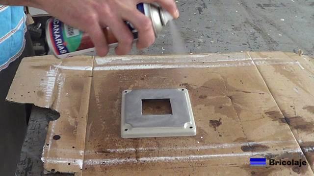 aplicando un barniz protector a la tapa metálica de la caja de registro